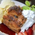 Bread Pudding with vanilla ice cream strawberries, whipped cream and raspberry sauce.